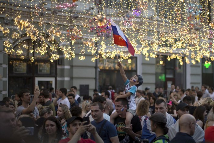A boy waves a Russian national flag as he walks with his relative and other soccer fans through Nikolskaya Street, a favourite meeting place for fans from different countries, during the 2018 soccer World Cup in Moscow, Russia. (AP/ PTI Photo)