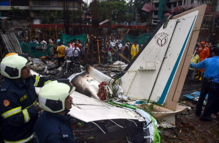 Fire-fighters work at the site of the chartered plane that crashed at Ghatkopar's Jivdaya Lane, in Mumbai on Thursday. Five persons were killed when a King Air C90 12-seater aircraft on a test flight crashed in a crowded Mumbai suburb. (PTI Photo)