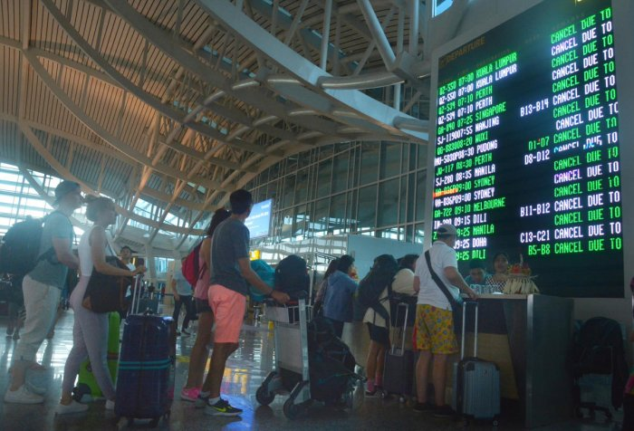 Passengers stand in front of a flight board after services were cancelled due to Mount Agung eruption at Ngurah Rai Airpot, in Bali, Indonesia, on Friday. (Reuters)