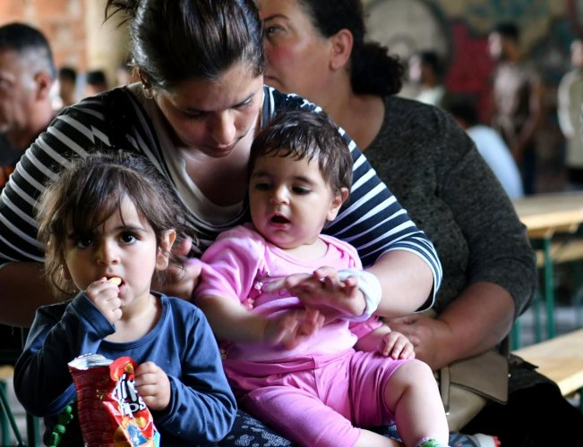 A mother sits with her children as they wait for lunch to be served at a makeshift migrant center, in the North-Western Bosnian town of Bihac, on May 31, 2018. Bosnia, one of Europe's poorest countries, is so ill-equipped to cope with a surging influx of