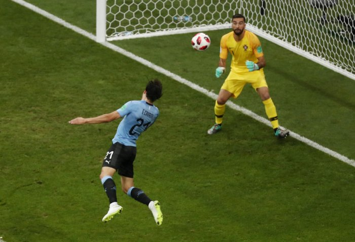 STUNNING MOVE: Edinson Cavani (left) heads home Uruguay's opening goal during their last 16 clash against Portugal's on Saturday. REUTERS