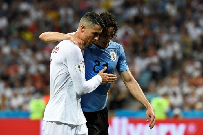 MATESHIP Edinson Cavani (right), who scored both of Uruguay's goals in their 2-1 win over Portugal, is helped off the pitch by his rival forward Cristiano Ronaldo. AFP
