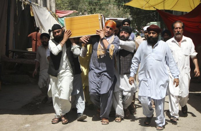 Sikh minorities carry the coffin of a relative killed in Jalalabad, Afghanistan. The Islamic State group has claimed responsibility for a suicide bombing in eastern Afghanistan that killed at least 19 people, mostly Sikhs and Hindus.