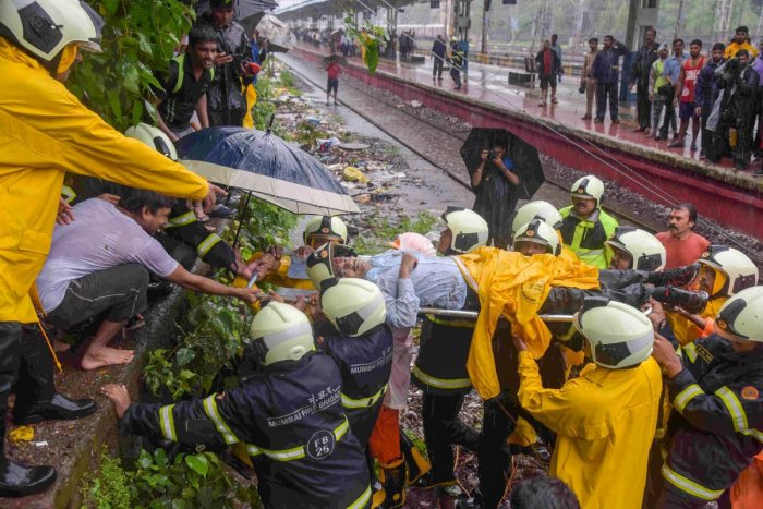Rescue workers carry an injured for treatments after a foot-overbridge collapsed on the railway tracks following heavy rains, at Andheri Station in Mumbai on Tuesday, July 3, 2018. (PTI Photo)