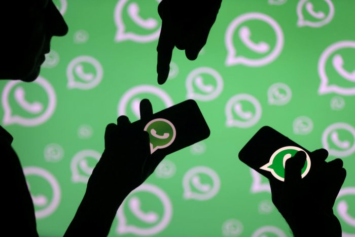 Men pose with smartphones in front of displayed Whatsapp logo, Reuters file photo