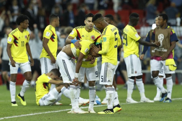 TOUGH NIGHT: Colombians players try to console each other after suffering an agonising loss to England on Tuesday. (AP/PTI Photo)
