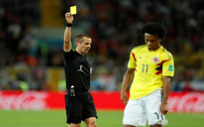 STRUGGLING FOR CONTROL: Referee Mark Geiger (left) brandishes the yellow card to Colombia's Juan Cuadrado. The Colombians, who resorted to rough play, earned six yellow cards in total. (Reuters Photo)