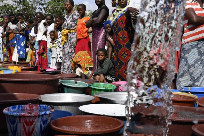 """A worker of the National Office of Drinking Water (ONEP) distributes water to the population on June 2, 2018 in a district of Bouake, central Ivory Coast, where the largest dam of the """"Societe de Distribution de l'Eau de la Cote d'Ivoire"""" (SODECI - Water"""