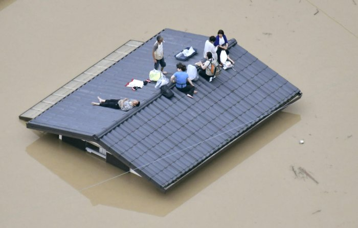 An aerial view shows local residents seen on the roof of a submerged house at a flooded area as they wait for a rescue in Kurashiki, southern Japan. (Reuters Photo)
