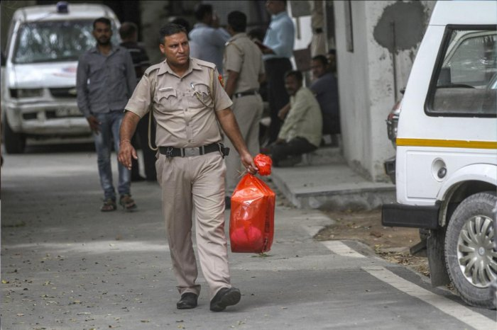 A policeman carries the postmortem reports, of the family of 11 members who were found hanging in their house in Burari, New Delhi. (PTI File Photo)