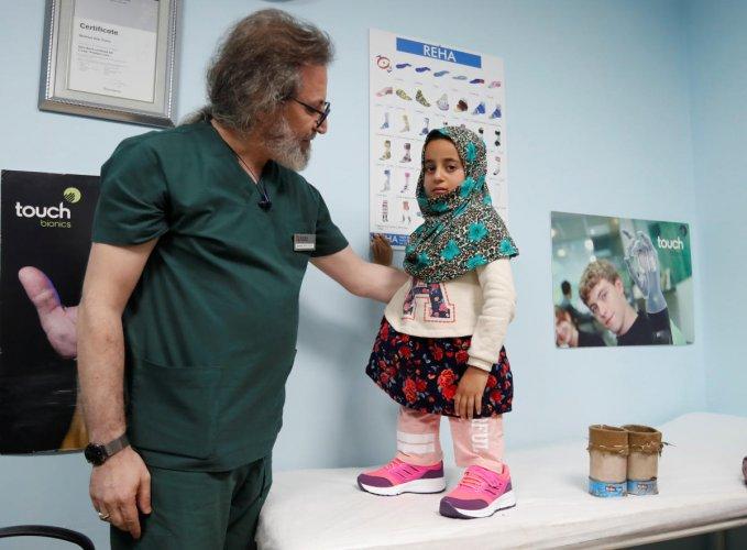 Prosthetics technician Mehmet Zeki Culcu adjusts artificial legs for Maya Meri at a prosthetic center in Istanbul. (Reuters Photo)
