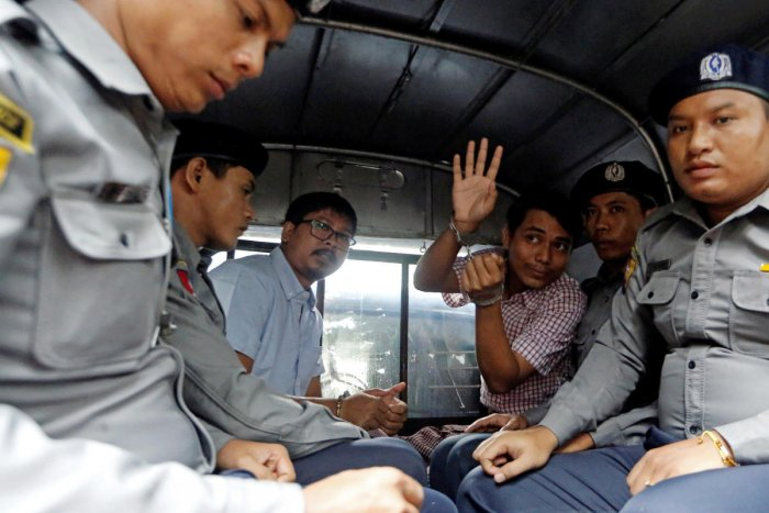 Detained Reuters journalist Wa Lone and Kyaw Soe Oo sit beside police officers as they leave Insein court in Yangon, Myanmar. (Reuters Photo)