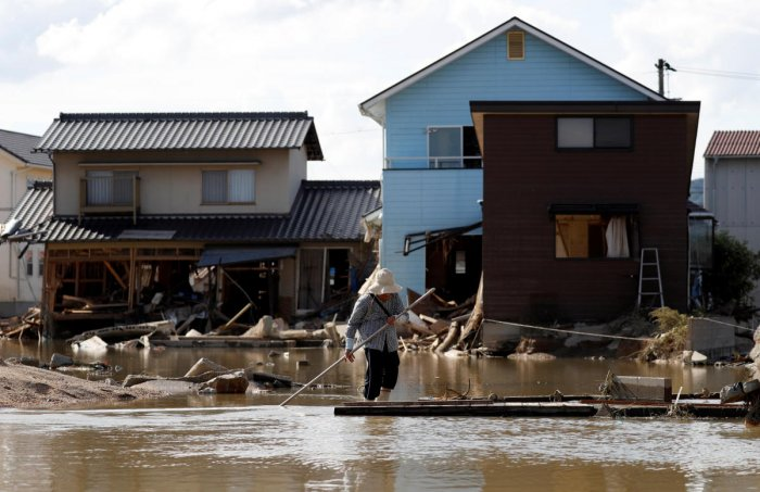 An elderly woman walks next to submerged and destroyed houses in a flooded area in Mabi town in Kurashiki, Okayama Prefecture, Japan. (Reuters Photo)