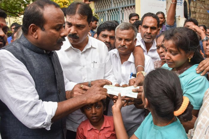 Mayor Sampath Raj hands over a cheque for 5 lakh to the wife of S Subramani at the KC General Hospital on Monday. dh Photo