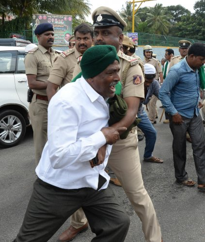 A policeman detains a protester near the Freedom Park on Monday. DH Photo/Satish Badiger