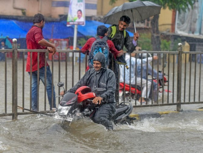 A man rides his motorcycle through a flooded road at King Circle after heavy downpour, in Mumbai on Tuesday, July 10, 2018. PTI Photo