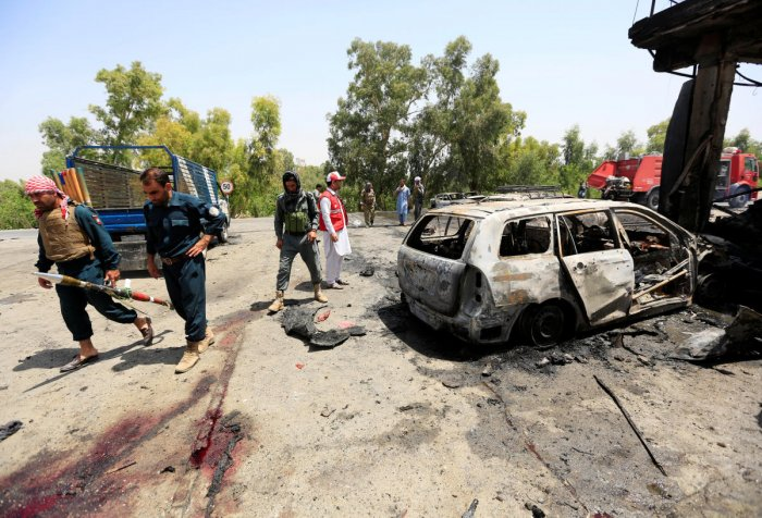 Afghan policemen inspect the site of a suicide attack in Jalalabad city, Afghanistan July 10, 2018. (REUTERS/Parwiz)