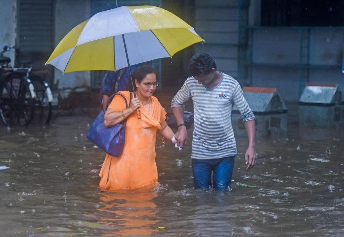 People make their way through flooded waters after heavy downpour at King Circle in Mumbai on Tuesday. PTI