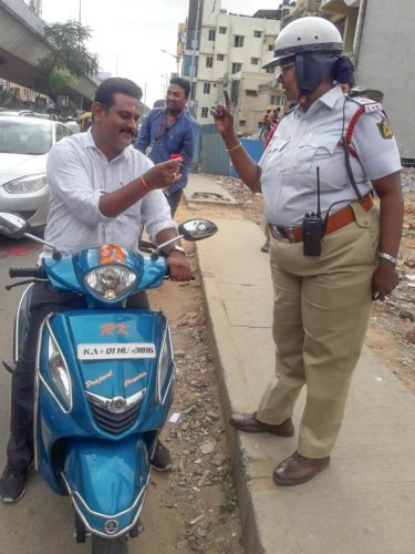 A policewoman hands over a rose to a traffic offender in Mico Layout on Tuesday. DH PhoTO