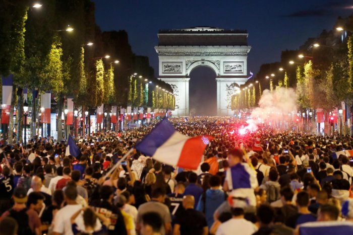 PARTY TIME French fans throng the Champs-Elysees on Tuesday night after the Les Blues stormed into the final of the World Cup. (Reuters Photo)