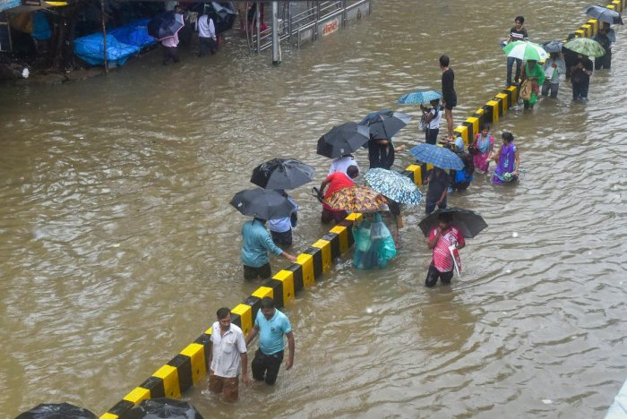 People wade through a waterlogged street following heavy rains, in Mumbai. PTI file photo