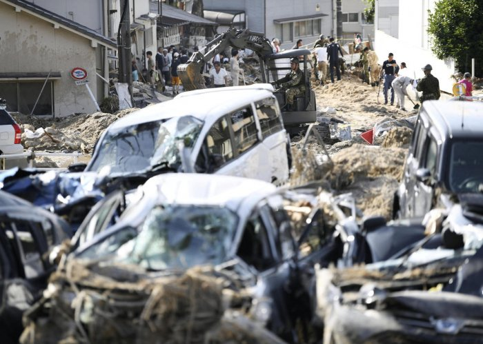 People clear debris caused by torrential rain at Aki ward in Hiroshima. Kyodo/Reuters.