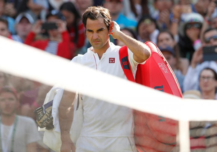 Roger Federer walks off court after loosing his quarter final match against South Africa's Kevin Anderson. Reuters
