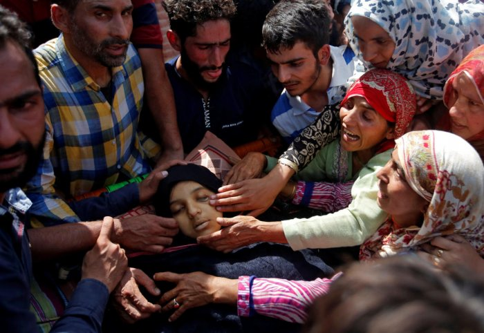 People react next to the body of 16-year-old girl Andleeb Jan, a civilian who according to local media died during clashes between protesters and Indian security forces, during her funeral i