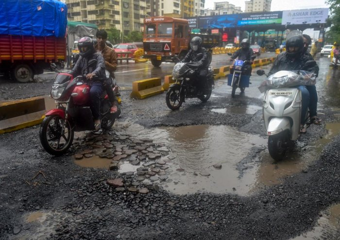 Commuters ride past pot-holes filled road after heavy rainfall, in Mumbai on Monday. (PTI file photo))