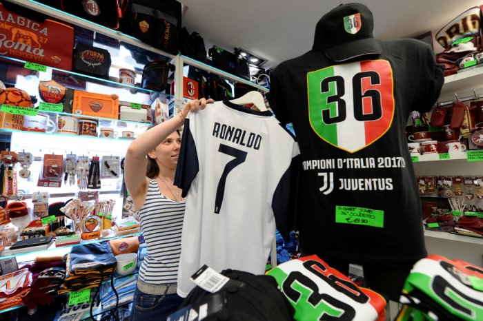 A woman adjusts a Juventus jersey with the name of Cristiano Ronaldo at a souvenir shop in Turin, Italy July 11, 2018. REUTERS