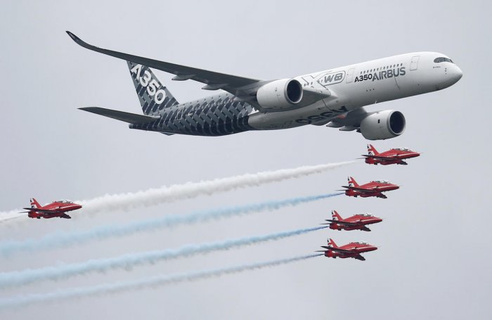 An Airbus A350 aircraft flies in formation with Britain's Red Arrows flying display team at the Farnborough International Airshow in Farnborough, Britain. (Reuters Photo)
