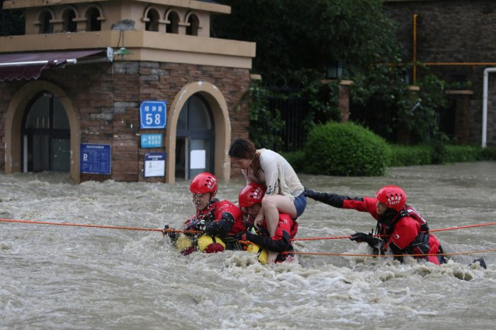 Firefighters rescue a stranded woman on a flooded street, following heavy rainfall in Chengdu, Sichuan province. Reuters Photo