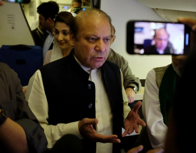 Ousted Pakistani Prime Minister Nawaz Sharif gestures as he boards a Lahore-bound flight due for departure, at Abu Dhabi International Airport. (Reuters Photo)