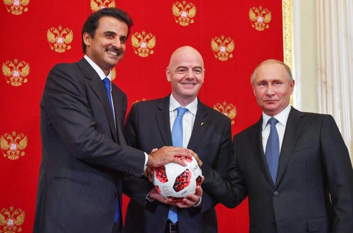 FIFA president Gianni Infantino (centre) takes the ball from Russian president Vladimir Putin (right) and passes it to Emir of Qatar Sheikh Tamim bin Hamad Al-Thani as a symbol of transfer of authority to Qatar for hosting the FIFA World Cup 2022. AFP