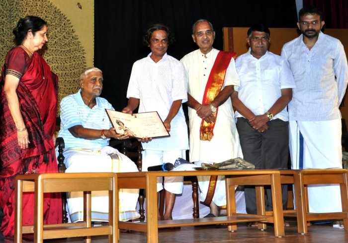 Veteran scholar Bannanje Govindacharya (2nd from left) honours senior Yakshagana artiste Bannanje Sanjeev Suvarna with the Yakshagana Kalaranga award at the Udupi Purabhavana on Sunday.