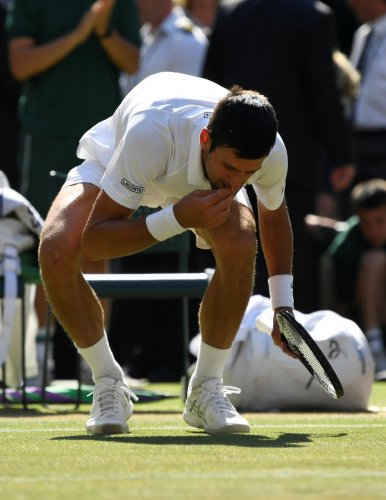 Serbia's Novak Djokovic eats grass from the court as he celebrates after winning the men's singles final against South Africa's Kevin Anderson. (REUTERS/Tony O'Brien)