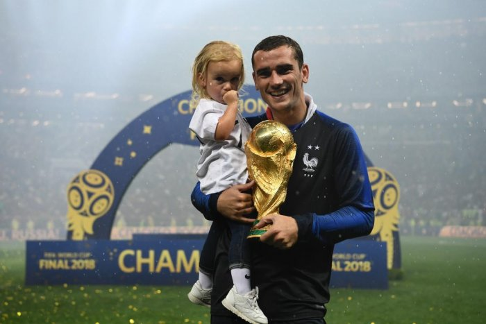 France's forward Antoine Griezmann poses with his daughter and their World Cup trophy after winning the Russia 2018 World Cup final football match between France and Croatia at the Luzhniki Stadium in Moscow on July 15, 2018. (AFP PHOTO)
