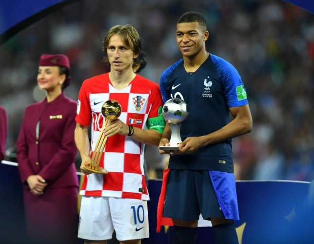 Croatia's Luka Modric poses with the World Cup Best Player Award as France's Kylian Mbappe poses with the World Cup Best Young Player Award. (REUTERS/Dylan Martinez)