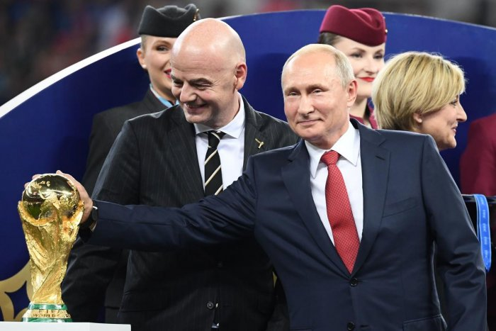 Russian president Vladimir Putin (left) touches the World Cup trophy during the post-match ceremony on Sunday. Also seen are FIFA president Gianni Infantino (left). AFP