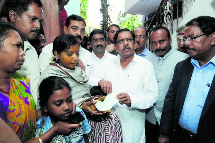 Deputy Chief Minister G Parameshwara hands over Rs 5 lakh compensation to the family of Subramani S, the pourakarmika who committed suicide for non-payment of salary for months, on Sunday. (DH Photo)