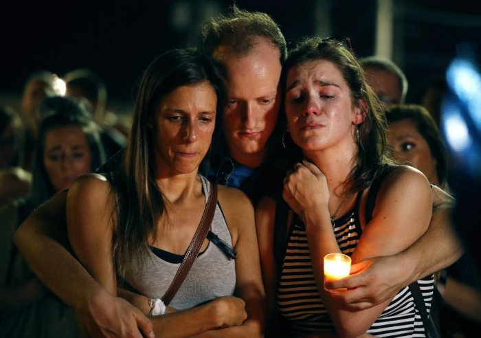 Mallory Cunningham, left, Santino Tomasetti, center, and Aubrey Reece attend a candlelight vigil in the parking lot of Ride the Ducks Friday, July 20, 2018, in Branson, Mo. One of the company's duck boats capsized Thursday night resulting in over a dozen deaths on Table Rock Lake. AP/PTI