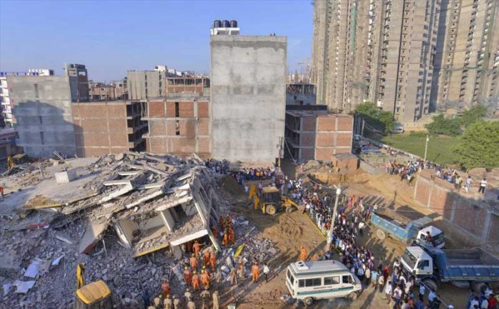 Greater Noida: NDRF and local authorities carry out rescue work at the site of a collapsed building at Shahberi village, in Greater Noida West on Wednesday, July 18, 2018. A six-storey under-construction building collapsed in Greater Noida, killing at least two persons and trapping several others under the debris. (PTI Photo)