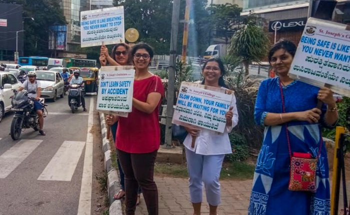 Residents hold placards on road safety during their campaign at Richmond Circle on Sunday.