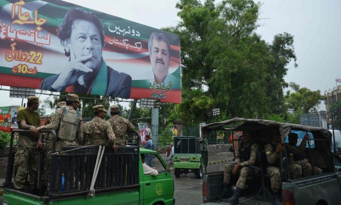 Pakistani soldiers patrol on a street beside a billboard featuring an image of Pakistani cricketer turned politician Imran Khan (top L) of the Pakistan Tehreek-e-Insaf (Movement for Justice), ahead of general election in Rawalpindi. AFP Photo