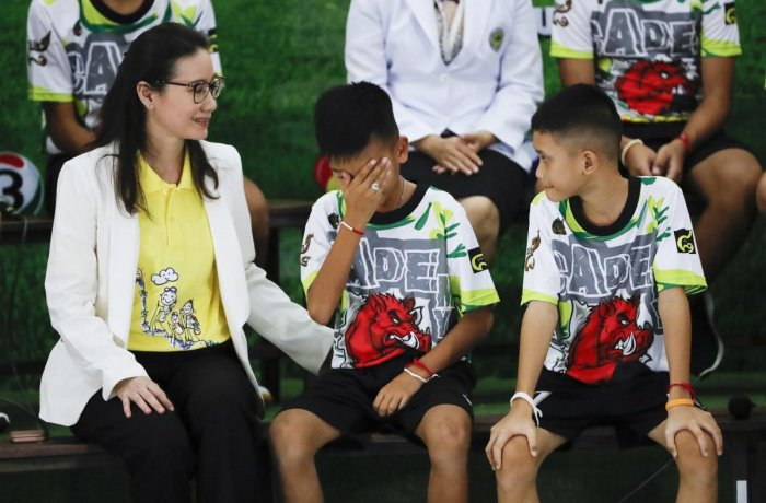 "Rescued soccer player ""Titan"" Chanin Vibulrungruang reacts after paying respect to a portrait of Saman Gunan, the Thai Navy SEAL diver who died in the rescue attempt, during a press conference discussing their ordeal in Chiang Rai, northern Thailand, Wedn"