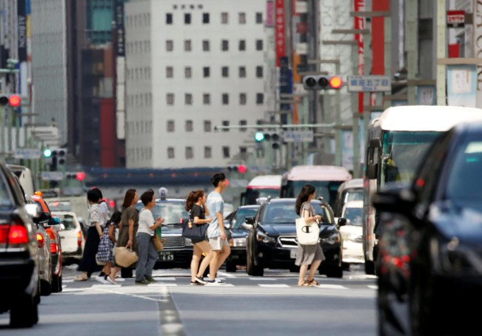 Passersby walk on a street in a heat haze during a heatwave in Tokyo, Japan July 23, 2018. REUTERS