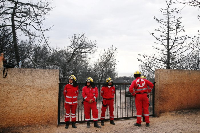 Rescue team members stand next to the area where bodies were found following a wildfire at the village of Mati, near Athens, Greece July 24, 2018. REUTERS/Costas Baltas