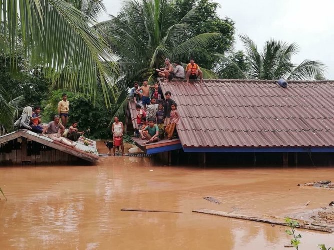 People take refuge on the roof of a house following a dam's collapse in Laos. Twitter photo.