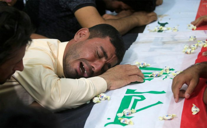 A man mourns at the funeral of the security men who were kidnapped and killed by Islamic State militants, in Kerbala, Iraq June 28, 2018. REUTERS/Alaa al-Marjani