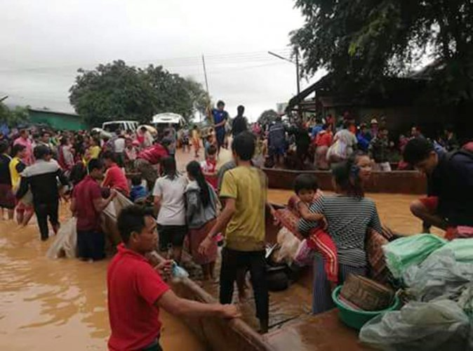 In this Tuesday, July 24, 2018, image from video, people are evacuated through the floodwaters from a collapsed dam in southeastern Laos. Rescue efforts are ongoing in villages flooded after part of a newly built hydroelectric dam was breached in southeas